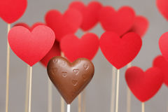 Valentine's day hearts on a stick with chocolate heart. Isolated on grey background Royalty Free Stock Image