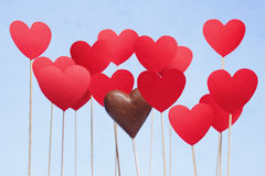 Valentine's day hearts on a stick with chocolate heart. Isolated on light blue background Stock Images
