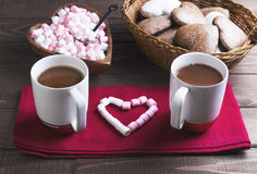 Valentine's Day holiday dinner romantic. On a wooden table wicker basket with chocolate cakes in the shape of hearts, two cups of hot chocolate, pink and white Royalty Free Stock Photos