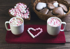 Valentine's Day holiday dinner romantic. On a wooden table wicker basket with chocolate cakes in the shape of hearts, two cups of hot chocolate, pink and white Stock Images
