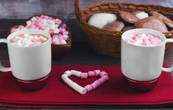Valentine's Day holiday dinner romantic. On a wooden table wicker basket with chocolate cakes in the shape of hearts, two cups of hot chocolate, pink and white Stock Image
