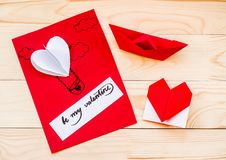 Valentine`s day holiday. hand made gift card with a heart balloon and an origami heart and paper boat on rustic background. Valentine`s day concept. hand made Royalty Free Stock Images
