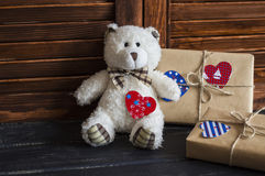 Valentine's day homemade gifts in craft paper with hearts tags, toy bear. On wooden rustic table Stock Photo
