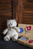 Valentine's day homemade gifts in craft paper with hearts tags, toy bear. On wooden rustic table Stock Photography