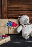 Valentine's day homemade gifts in craft paper with hearts tags, toy bear. On wooden rustic table Royalty Free Stock Photo