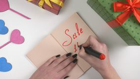 Valentine`s Day, illustration, woman`s hand writes in a dark brown notebook, sale 15 percent off 60 fps stock video