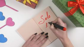 Valentine`s Day, illustration, woman`s hand writes in a dark brown notebook, sale 10 percent off 60 fps stock video footage
