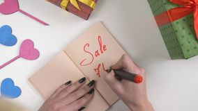 Valentine`s Day, illustration, woman`s hand writes in a dark brown notebook, sale 70 percent off. 60 fps stock video