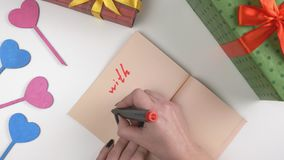 Valentine`s Day, illustration, woman`s hand writes in a dark brown notebook, With Love 60 fps. Valentine`s Day, illustration, woman`s hand writes in a notebook stock video