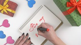 Valentine`s Day, illustration, woman`s hand writes in a notebook, Be my Valentine 60 fps. Valentine`s Day, illustration, woman`s hand writes in a dark brown stock footage