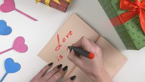 Valentine`s Day, illustration, woman`s hand writes in a dark brown notebook, Love is in the air 60 fps. Valentine`s Day, illustration, woman`s hand writes in a stock footage