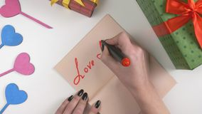Valentine`s Day, illustration, woman`s hand writes in a dark brown notebook, Love menu! 60 fps. Valentine`s Day, illustration, woman`s hand writes in a notebook stock footage
