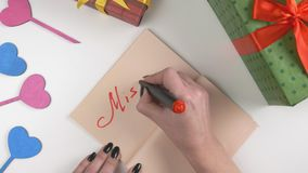 Valentine`s Day, illustration, woman`s hand writes in a dark brown notebook, Miss you 60 fps. Valentine`s Day, illustration, woman`s hand writes in a notebook stock video footage