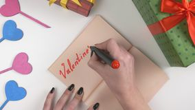 Valentine`s Day, illustration, woman`s hand writes in a dark brown notebook, Valentine`s Day sale 60 fps. Valentine`s Day, illustration, woman`s hand writes in a stock footage