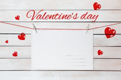 Valentine`s day lettering and postcards on red threads surrounded by hearts on wooden white background.  stock image