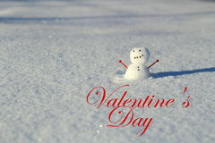 Valentine's day: Little snowman in the snow outside with heart arm. Valentine's day: Little snowman in the snow outside with the phrase Valentine's Day Royalty Free Stock Photos