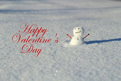 Valentine's day: Little snowman in the snow outside with heart arm. Valentine's day: Little snowman in the snow outside with the phrase Happy Valentine's day Stock Photo