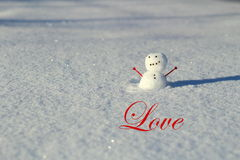 Valentine's day: Little snowman in the snow outside with heart arm. Valentine's day: Little snowman in the snow outside with the word love Royalty Free Stock Images