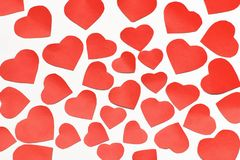Valentine`s day. Lots of red cut out hearts of different sizes on a white background. royalty free stock photo