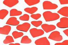 Valentine`s day. Lots of red cut out hearts of different sizes on a white background. royalty free stock photos