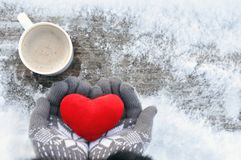 Valentine`s day and Love frosty picture: a Cup of hot coffee on a wooden bench and hands in knitted gray gloves hold a plush red royalty free stock photography