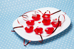 Valentine's day love gelatin deserts. Plate of Valentine's day love gelatin deserts with red and white hearts and ribbon on blue with dots (polka dot) background Stock Images