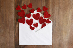 Valentine`s Day Love Letter Spilling out Red Hearts onto Wood Ba Stock Image