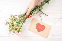 Valentine`s day love letter on wooden background. Brown envelop,. Pink note and gift box on table. Female hands with red nail polish stock images