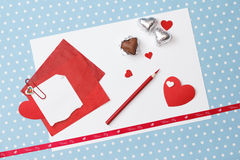 Valentine's day love message, unfinished. On white paper with pencil, red hearts in silver foil  on blue with white dots background (polka dot Stock Photo