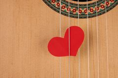 Valentine`s Day and love music concept. Red hearts on the strings of a guitar, close-up. Hearts are a symbol of love Stock Photo