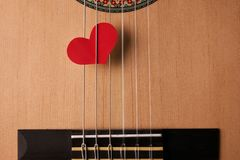 Valentine`s Day and love music concept. Red hearts on the strings of a guitar, close-up. Hearts are a symbol of love Stock Images