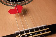 Valentine`s Day and love music concept. Red hearts on the strings of a guitar, close-up. Hearts are a symbol of love Stock Image