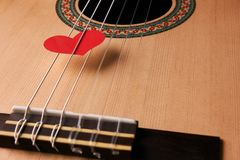 Valentine`s Day and love music concept. Red hearts on the strings of a guitar, close-up. Hearts are a symbol of love Stock Photography