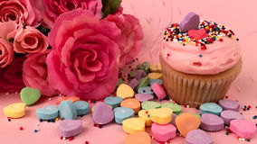 Valentine's Day Love Scene with Candy Hearts Flowers Cupcake. Valentine's Day scene with colorful candy hearts next to cupcake with bouquet of pink roses gets stock video footage