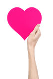 Valentine's Day and love theme: hand holding a pink heart isolated on a white background Royalty Free Stock Images
