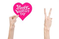 Valentine's Day and love theme: hand holds a greeting card in the form of a pink heart with the words Happy Valentine's day Stock Photos