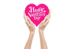 Valentine's Day and love theme: hand holds a greeting card in the form of a pink heart with the words Happy Valentine's day. Isolated on white background Royalty Free Stock Photography