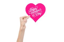 Valentine's Day and love theme: hand holds a greeting card in the form of a pink heart with the words Happy Valentine's day. Isolated on white background Royalty Free Stock Photos