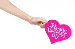 Valentine's Day and love theme: hand holds a greeting card in the form of a pink heart with the words Happy Valentine's day Royalty Free Stock Image