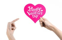 Valentine's Day and love theme: hand holds a greeting card in the form of a pink heart with the words Happy Valentine's day Royalty Free Stock Images