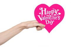 Valentine's Day and love theme: hand holds a greeting card in the form of a pink heart with the words Happy Valentine's day Stock Image