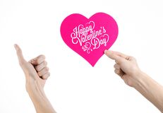 Valentine's Day and love theme: hand holds a greeting card in the form of a pink heart with the words Happy Valentine's day Stock Photography