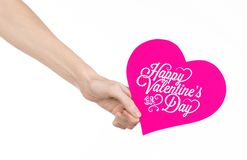 Valentine's Day and love theme: hand holds a greeting card in the form of a pink heart with the words Happy Valentine's day Royalty Free Stock Photo