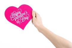 Valentine's Day and love theme: hand holds a greeting card in the form of a pink heart with the words Happy Valentine's day Royalty Free Stock Photography