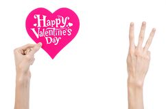 Valentine's Day and love theme: hand holds a greeting card in the form of a pink heart with the words Happy Valentine's day Royalty Free Stock Photos