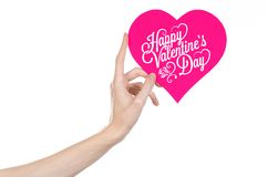 Valentine's Day and love theme: hand holds a greeting card in the form of a pink heart with the words Happy Valentine's day. Isolated on white background Stock Photos