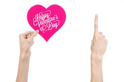 Valentine's Day and love theme: hand holds a greeting card in the form of a pink heart with the words Happy Valentine's day. Isolated on white background Royalty Free Stock Image