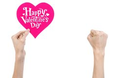Valentine's Day and love theme: hand holds a greeting card in the form of a pink heart with the words Happy Valentine's day Stock Photo