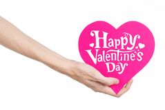 Valentine's Day and love theme: hand holds a greeting card in the form of a pink heart with the words Happy Valentine's day Stock Images