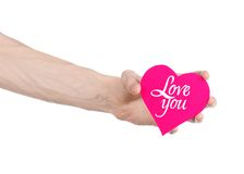 Valentine's Day and love theme: hand holds a greeting card in the form of a pink heart with the words Love you isolated. On white background Royalty Free Stock Images